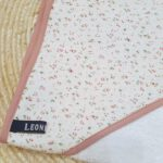Badcape met kleine roosjes. de rand heeft de kleur van oud roze
